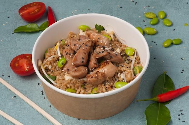 Riz à l'ail avec du poulet et des haricots dans un bol artisanal. concept: livraison de nourriture