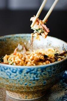 Riz asiatique avec viande de porc, champignons mu-err, chou napa, pousses de bambou marinées, épinards, teriyaki, sauce chili douce, chips d'oignon dans un bol en céramique.