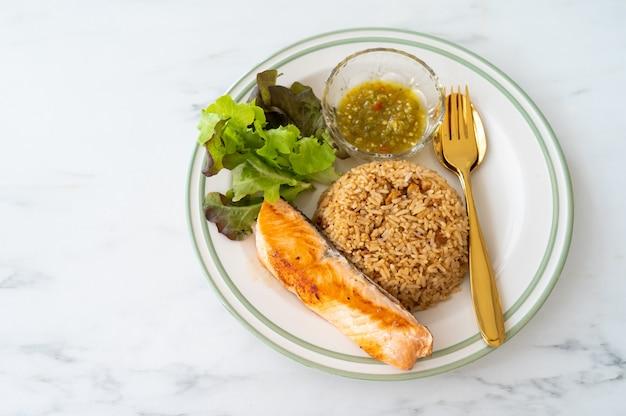 Riz au crabe avec saumon grillé sur table