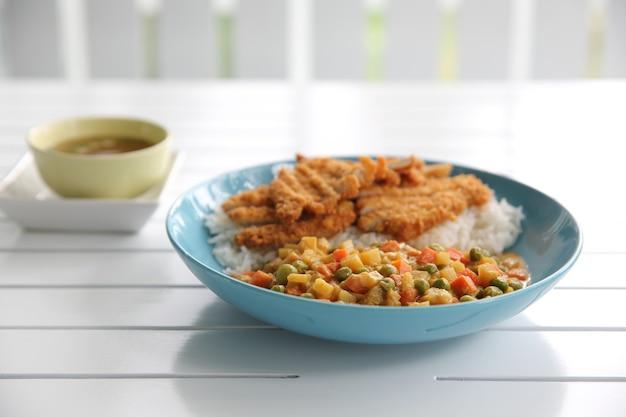 Riz au curry de cuisine japonaise avec du porc frit sur fond de bois