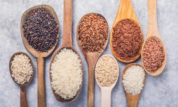 Riz au jasmin blanc biologique, riz noir et brun non poli, riceberry dans des cuillères en bois