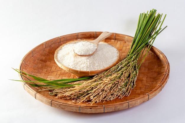 Riz au jasmin thaï dans un bol en bois et riz isolé sur fond blanc