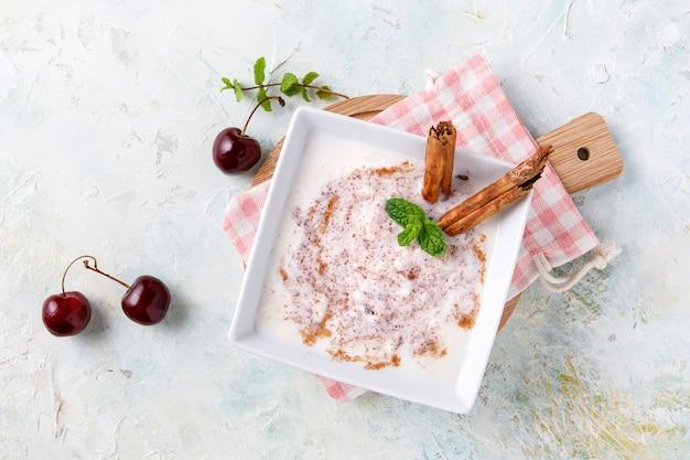 Riz au lait fait maison à la cannelle et aux cerises dans un bol blanc sur bois