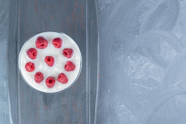 Riz au lait garni de framboises dans un bol sur un plateau bleu marine sur table en marbre.