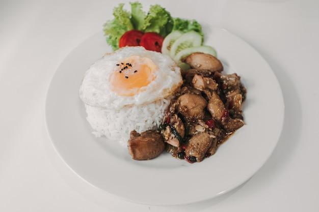 Riz au poulet frit au basilic et oeuf au plat servi sur un plat blanc