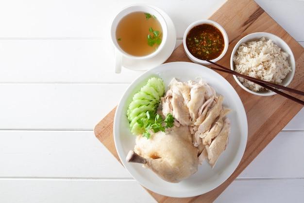 Riz au poulet hainan, poulet cuit à la vapeur avec du riz, khao mun kai sur fond de bois