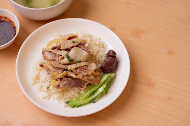 Riz au poulet avec sauce et soupe sur le côté gauche de la table en bois