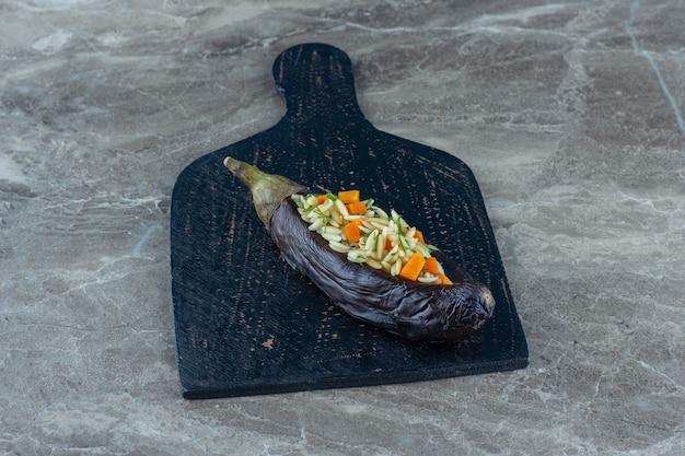 Riz aux aubergines sur la planche à découper, sur la table en marbre.