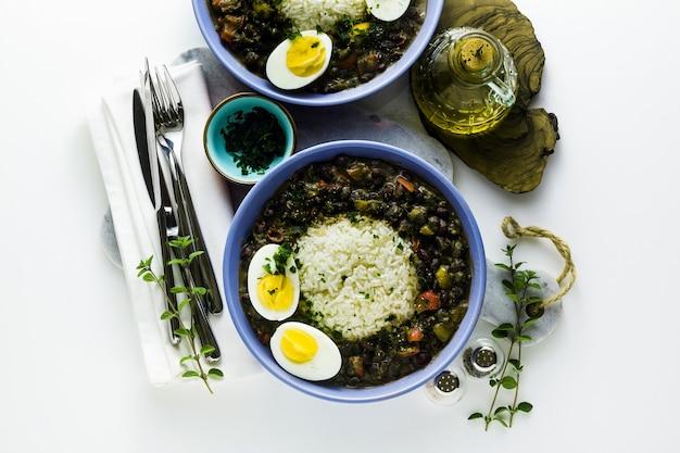 Riz aux haricots noirs et œuf à la coque sur la table avec des épices et de l'huile d'olive