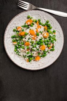 Riz aux haricots verts et carottes sur une assiette près de la fourchette