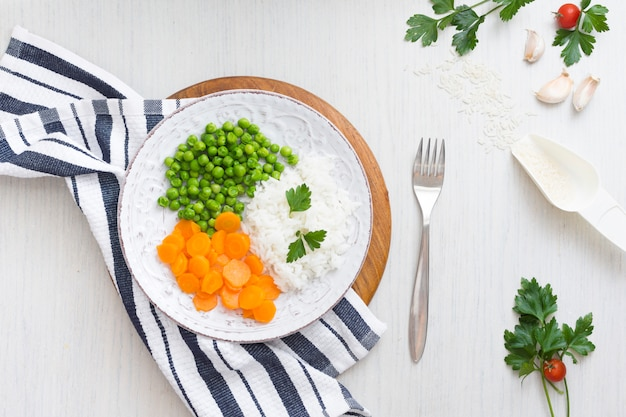Riz aux légumes sur une planche de bois près de serviette et fourchette