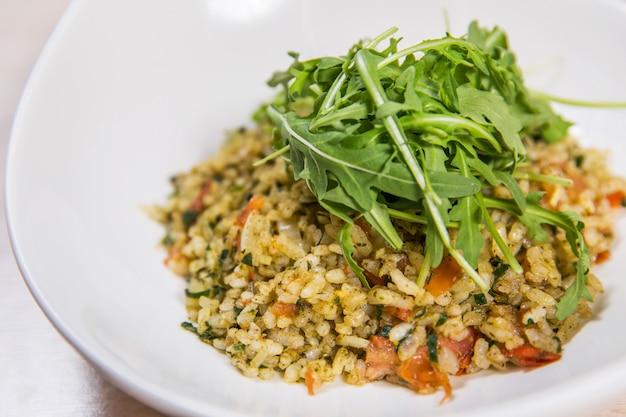 Riz aux légumes et à la roquette dans une assiette blanche sur une table en bois clair dans un restaurant