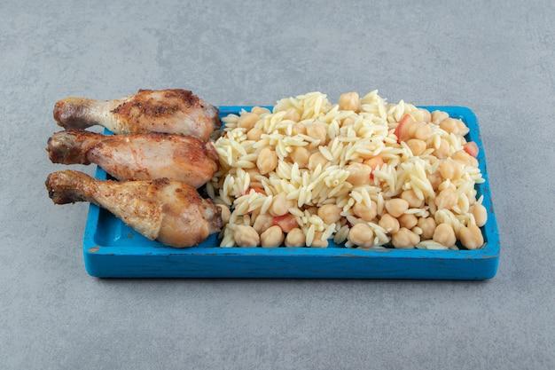 Riz aux pois chiches et cuisses de poulet sur plaque bleue.