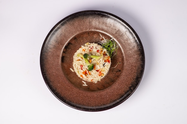 Riz basmati avec carottes frites, oignons, champignons, légumes brocolis sur une surface blanche