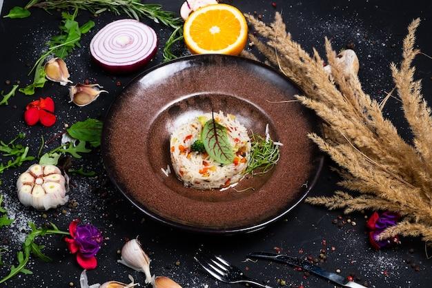 Riz basmati avec carottes frites, oignons, champignons, légumes brocolis sur une surface sombre