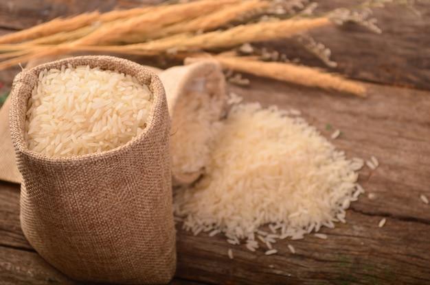 Riz blanc au jasmin dans un petit sac de jute sur bois