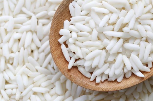 Riz blanc biologique dans une cuillère en bois, riz gluant ou riz gluant.