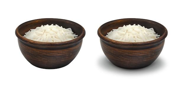 Riz blanc bouilli dans un bol d'argile simple sur fond blanc, isolé et avec une ombre