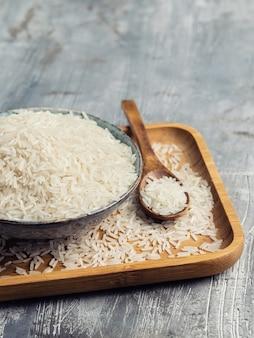 Riz blanc cru dans un bol en céramique avec une cuillère en bois sur fond gris