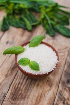 Riz blanc cru dans un bol avec des feuilles de basilic frais sur une planche en bois patinée