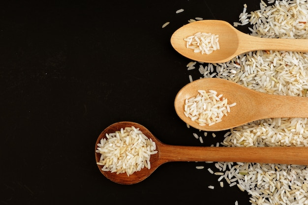Riz blanc cru avec trois cuillère en bois sur fond noir
