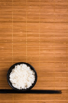 Riz blanc cuit à la vapeur dans un bol en céramique noire avec des baguettes