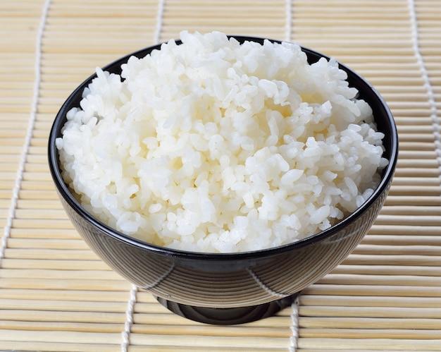 Riz blanc cuit à la vapeur dans un bol rond noir