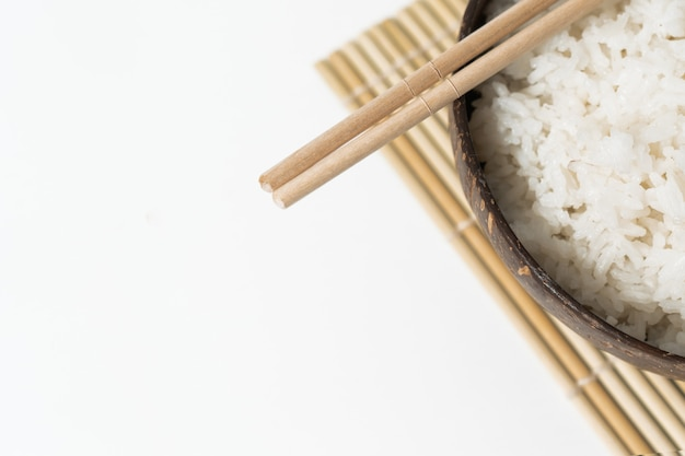 Riz blanc dans un bol de noix de coco sur fond blanc. photo minimaliste avec des baguettes de riz et de bambou.