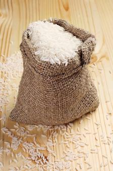 Riz blanc dans un sac sur table en bois
