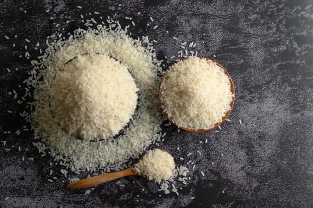 Riz blanchi dans un bol et une cuillère en bois sur le sol en ciment noir.