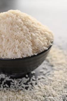 Riz blanchi dans un bol noir sur le sol en ciment noir.