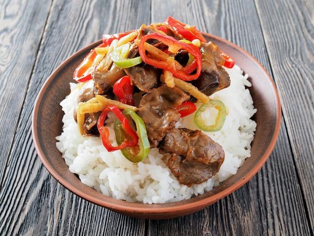 Riz bouilli à l'asiatique avec abats de poulet et chili