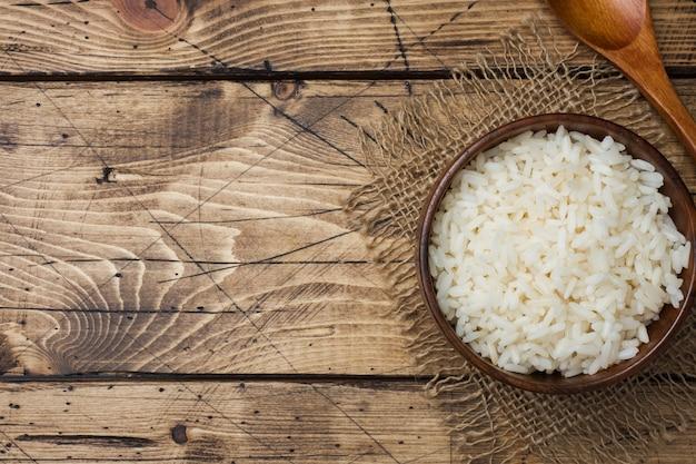 Riz bouilli blanc dans un bol en bois. style rustique.