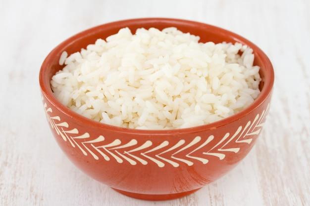 Riz bouilli dans un bol sur fond blanc