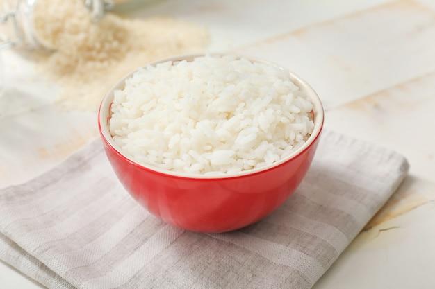 Riz bouilli dans un bol sur une table en bois blanc