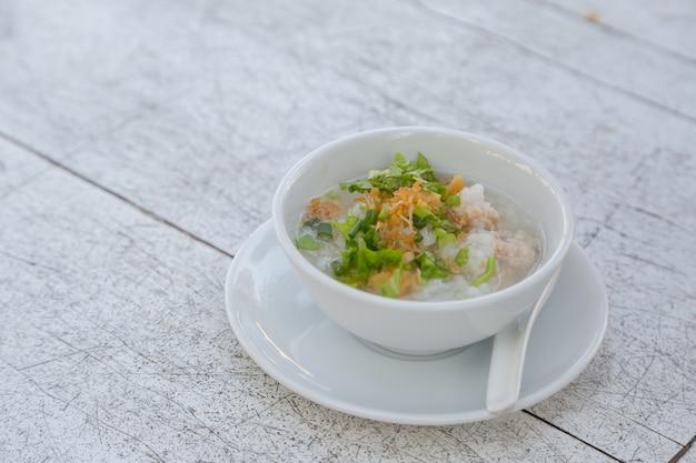 Riz bouilli avec du porc dans un bol blanc sur fond de table en bois blanc