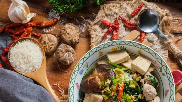 Riz bouilli avec du porc, os de porno et saucisse de porc thaïlandaise dans un bol.