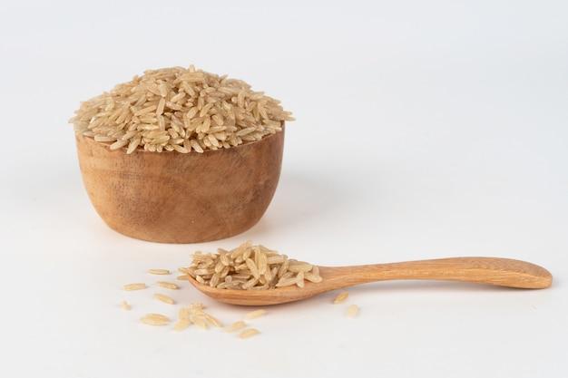 Riz brun dans un bol en bois et cuillère débordant et éparpillés sur le sol.