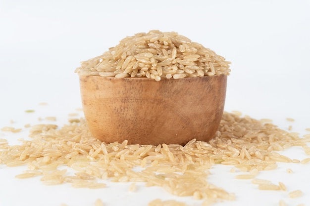 Riz brun dans un bol en bois débordant et éparpillé sur le sol.