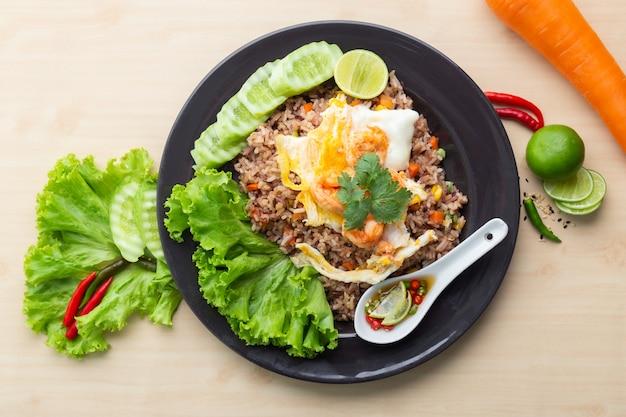 Riz brun frit aux crevettes et œuf au plat en thaï