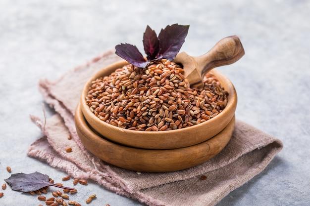 Riz brun non poli dans un bol en bois. fond de riz à grain long.