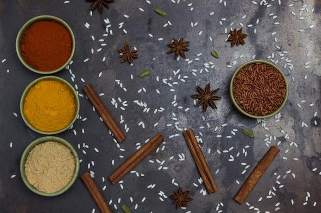 Riz brun rouge dans un bol en céramique verte. gingembre, curcuma, poivre dans des bols. bâtonnets d'anis étoilé et de cannelle.