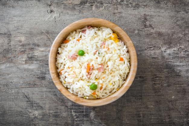 Riz chinois frit aux légumes sur la vue de dessus de table en bois