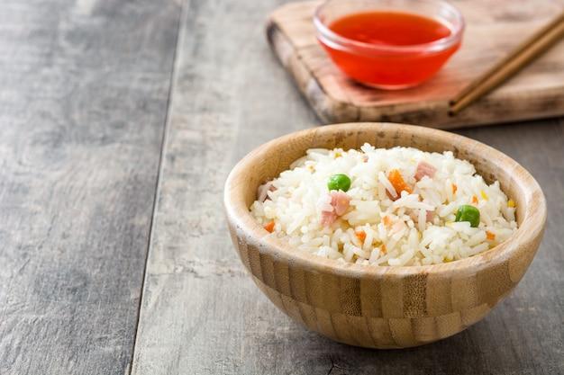Riz chinois frit avec des légumes sur l'espace de copie de table en bois