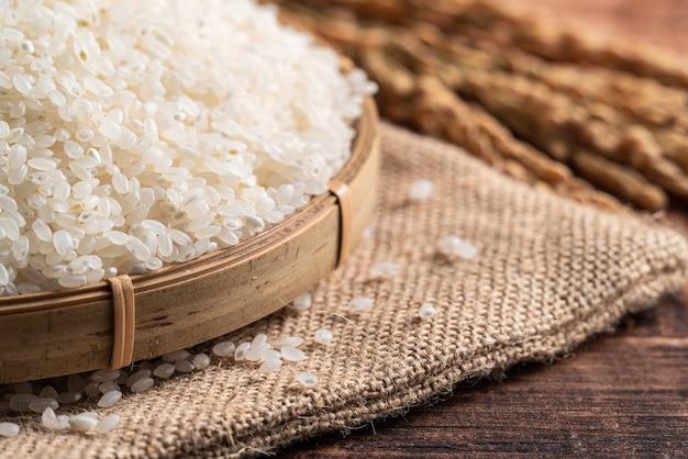 Riz comestible frais poli blanc cru sur fond de table en bois dans un bol, concept de design organique.