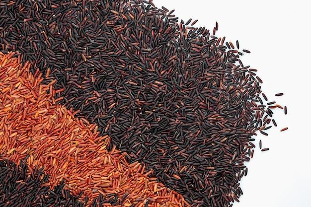Riz cru avec deux rangées de riz noir et rouge pour fond d'isolat blanc