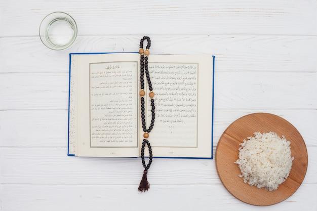 Riz cuit avec coran et perles sur une table lumineuse
