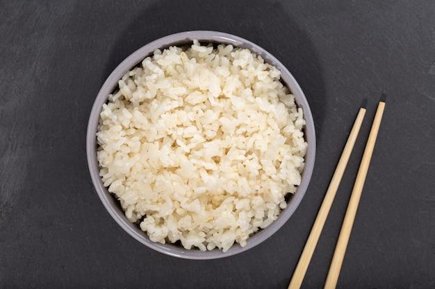 Riz cuit dans un bol et baguettes sur ardoise noire. vue de dessus