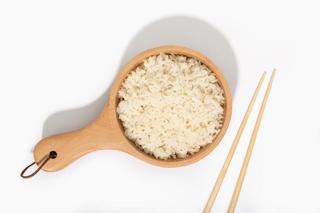 Riz cuit dans une cuillère en bois et des baguettes sur fond blanc. vue de dessus