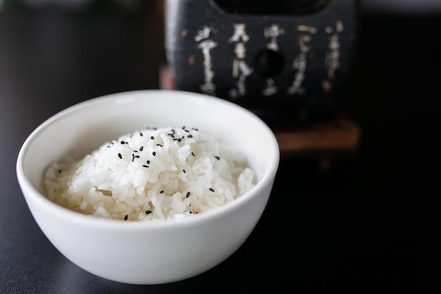 Riz cuit japonais dans un bol blanc sur un tableau noir.